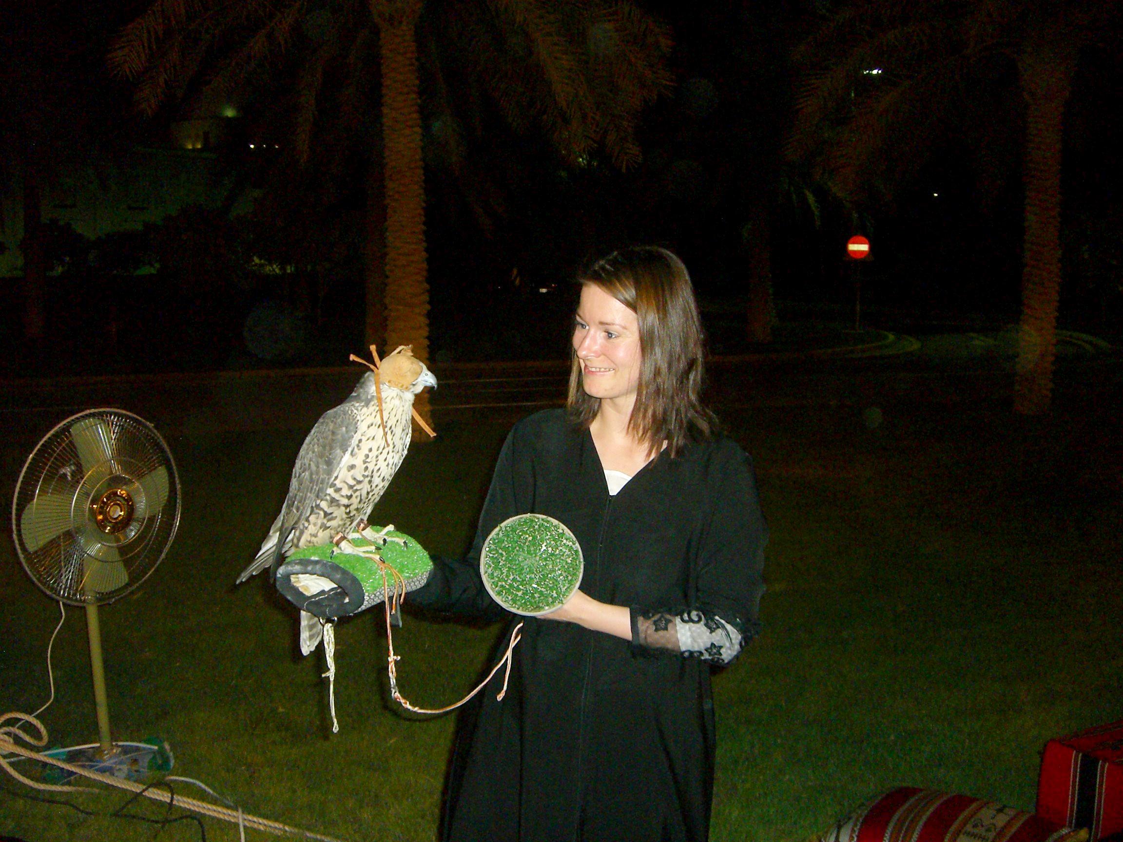 Eine Frau hat einen Falken auf dem Arm.