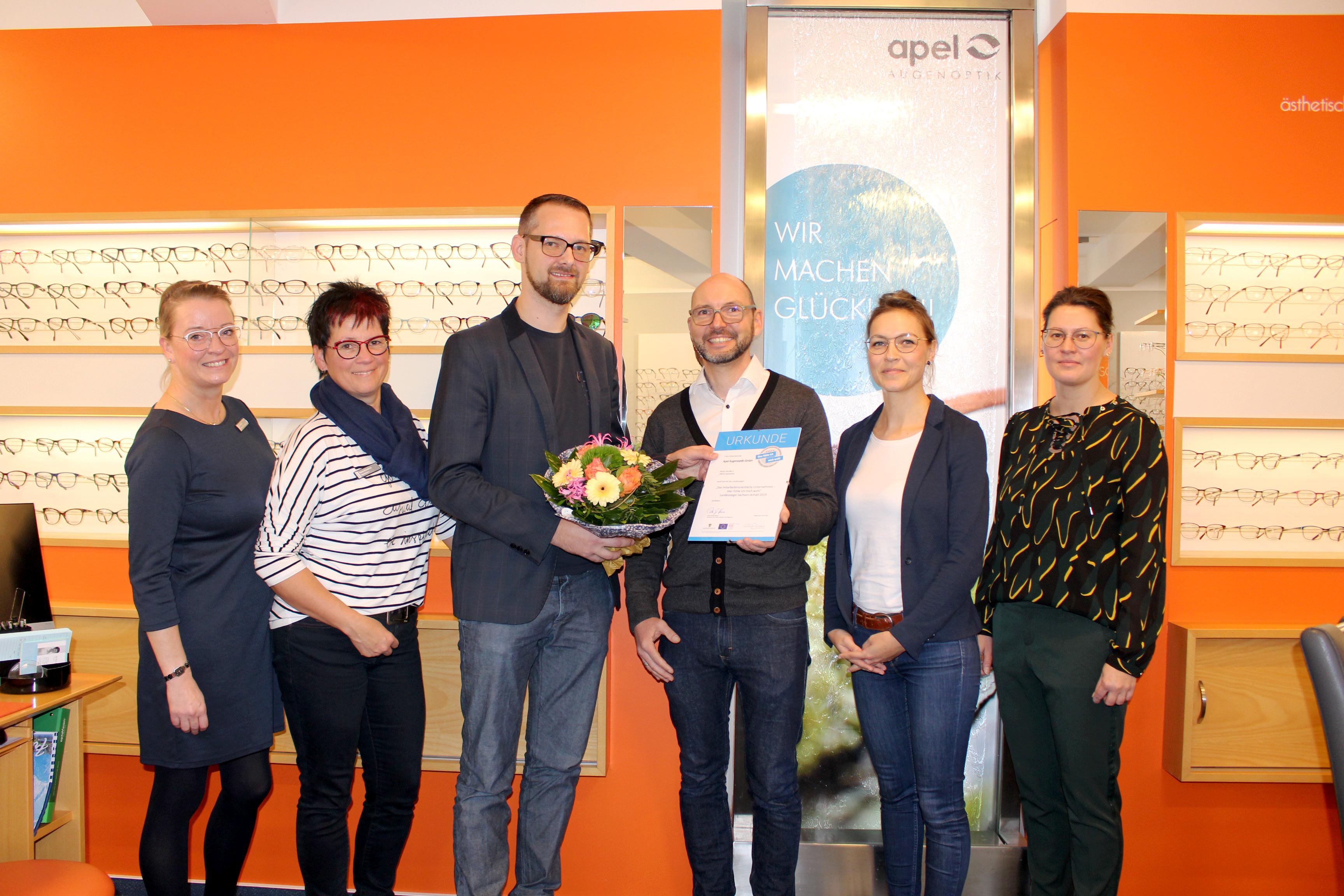 Das Team von Apel Augenoptik, 4 Frauen und ein Mann stehen vor einem Regal mit Brillen. Der Mann in der Mitte bekommt die Urkunde und einen Blumenstrauß durch Heiko Wisny der Landesinitiative überreicht.