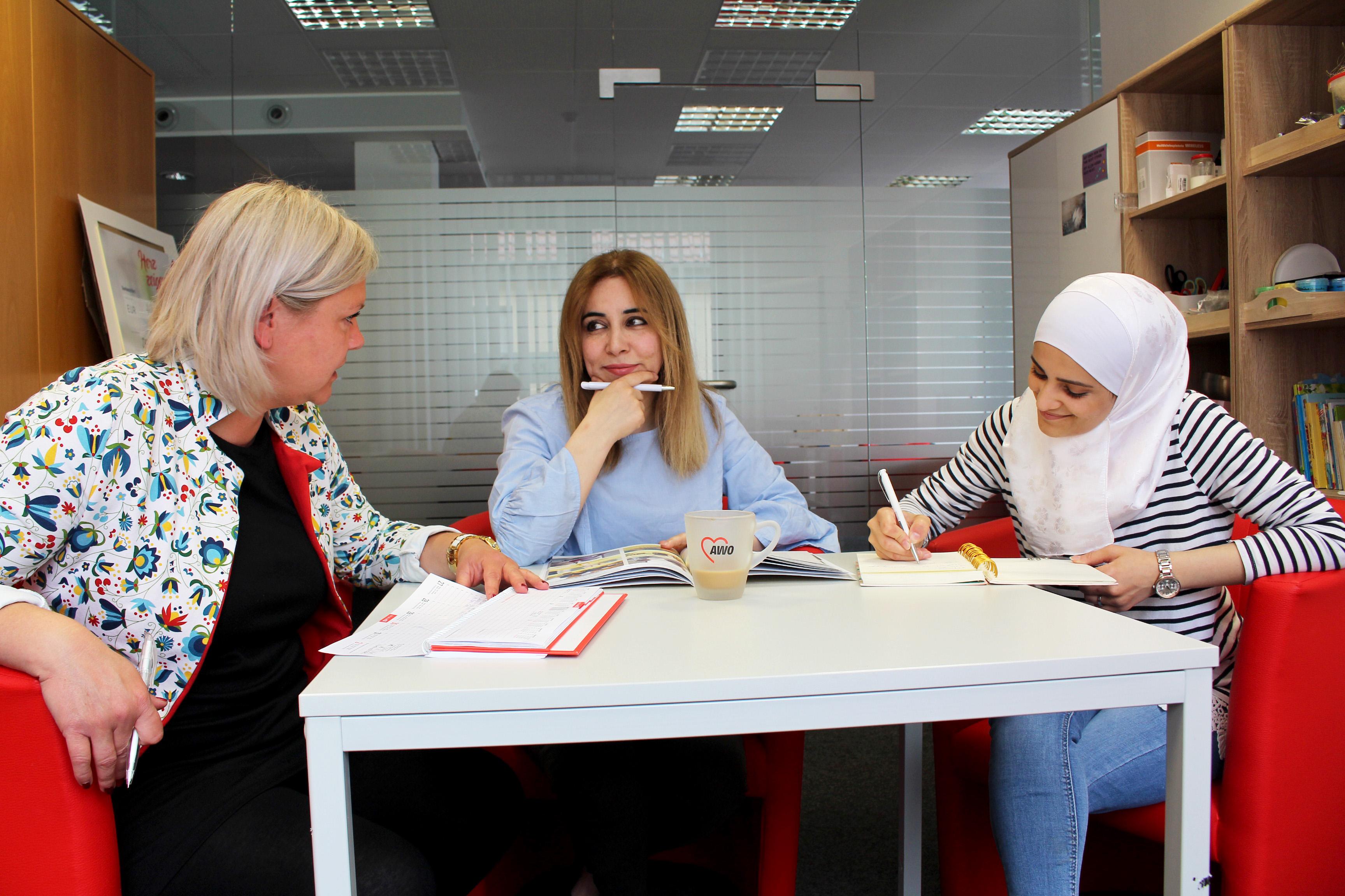 Drei Frauen sitzen an einem Tisch und reden miteinander.