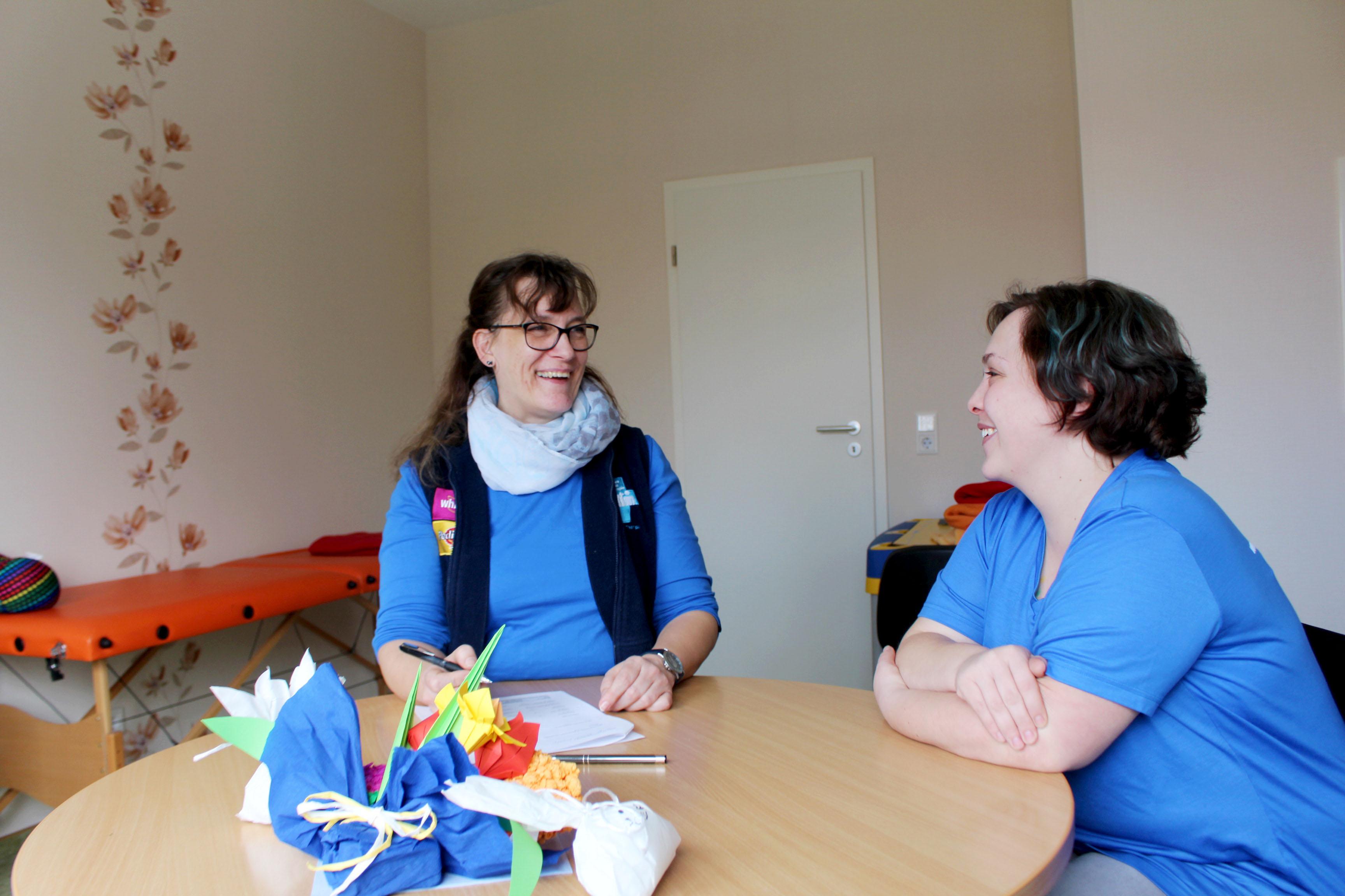 Zwei Frauen sitzen am Tisch und unterhalten sich.