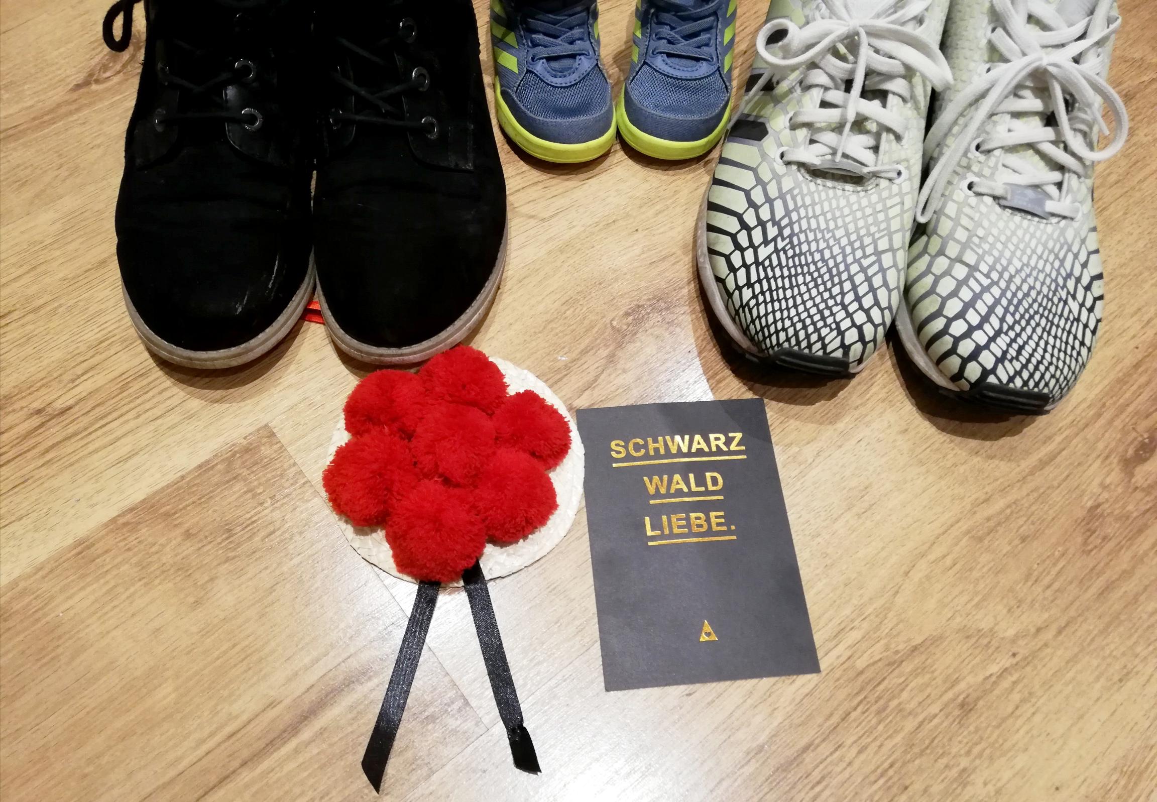 Blick von oben auf 3 Paar Schuhe, darunter ei Paar Kinderschuhe, ein kleiner Schwarzwald hut und einer Postkarte auf der Schwarzwaldliebe steht