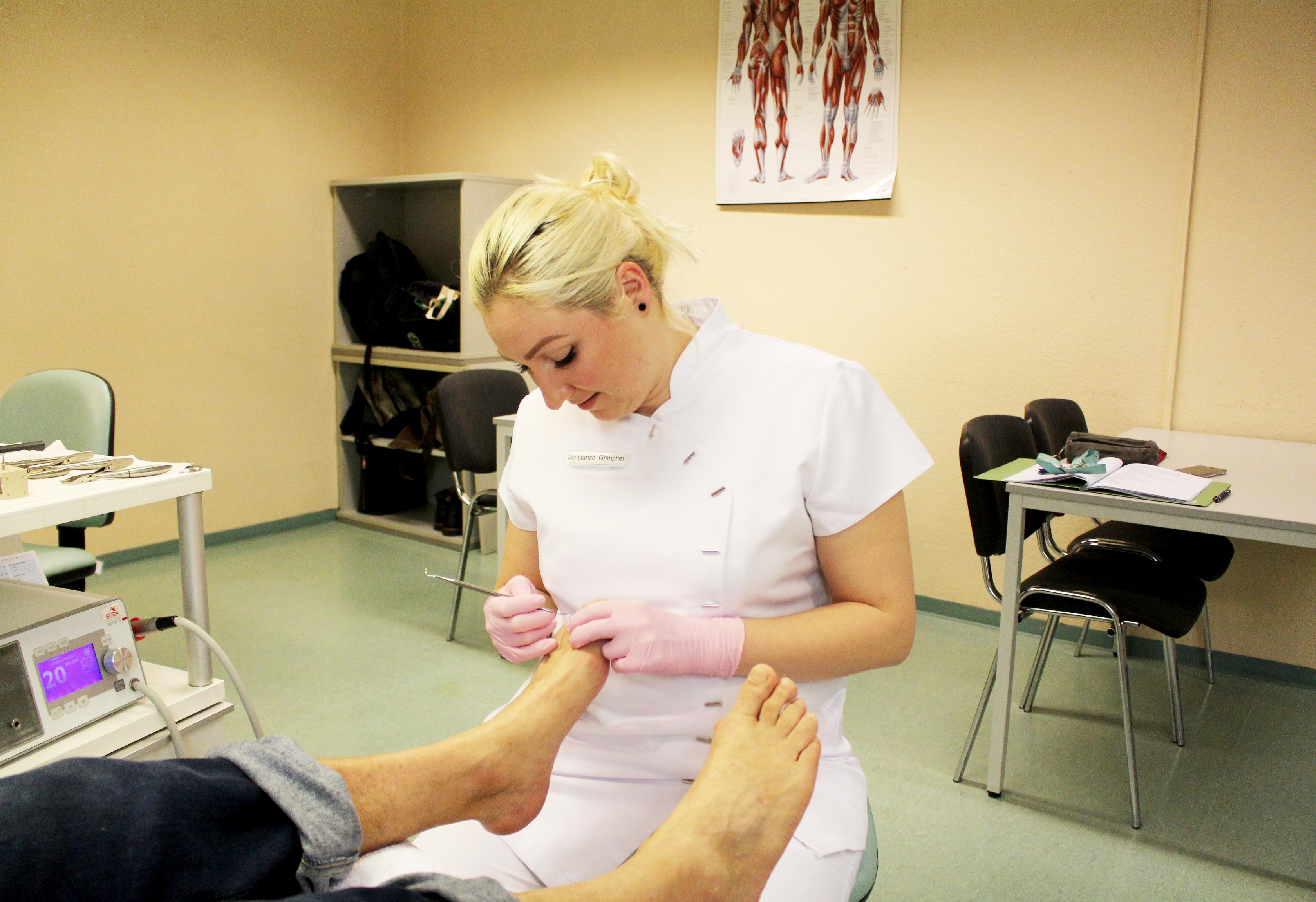 Eine Frau sitzt und pflegt die Füße von jemanden.