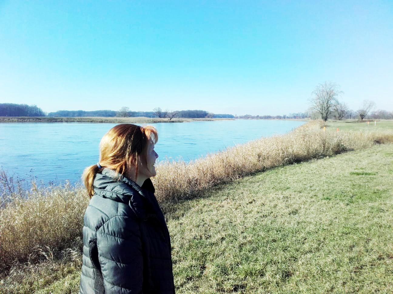 Eine Frau im Vordergrund steht auf einem Deich an der Elbe.