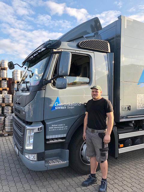 Ein junger Mann steht vor einem grauen LKW der Getränkehandel Köthen GmbH