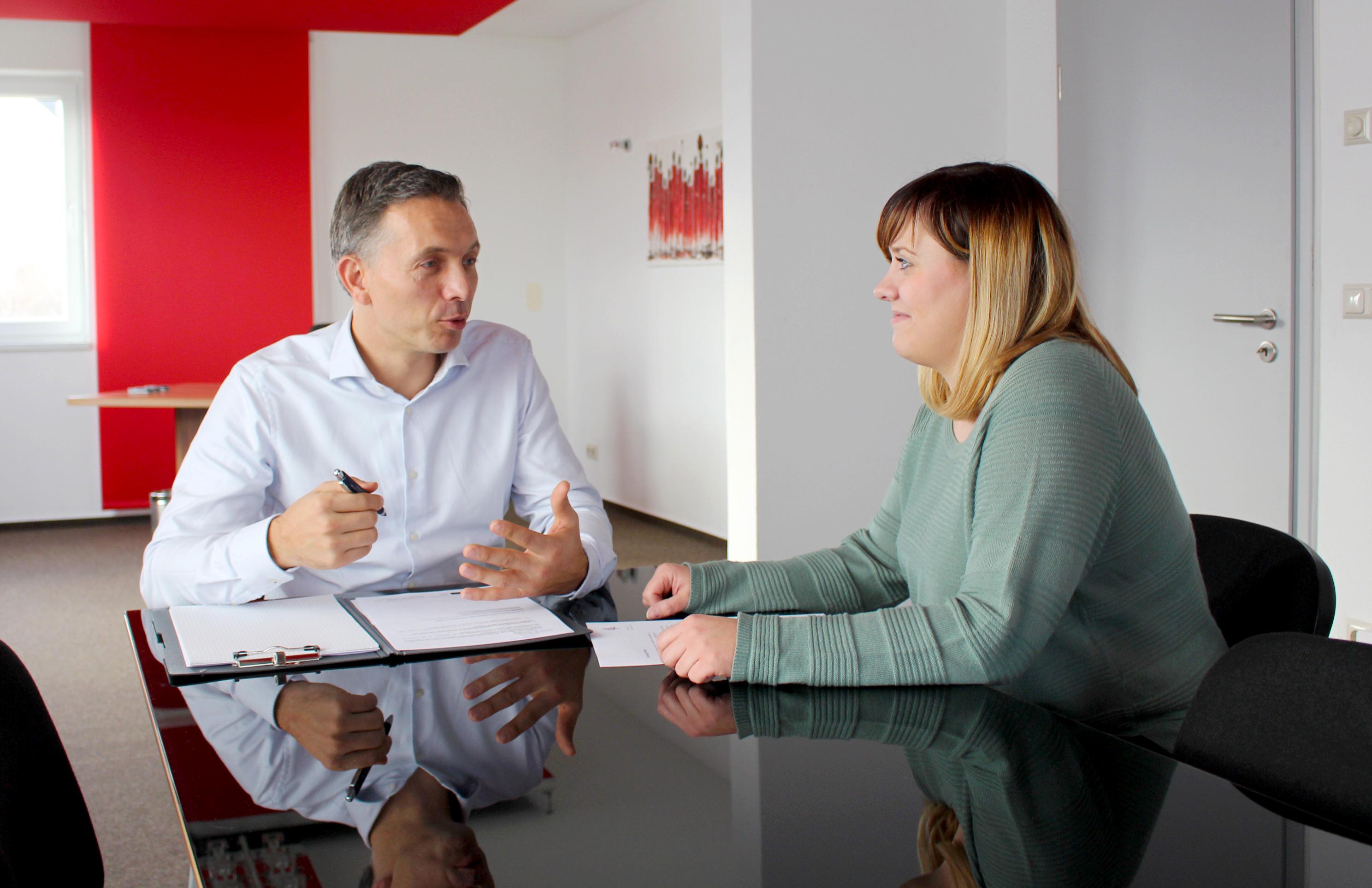 Ein Mann links und eine Frau rechts sitzen am Tisch und unterhalten sich.