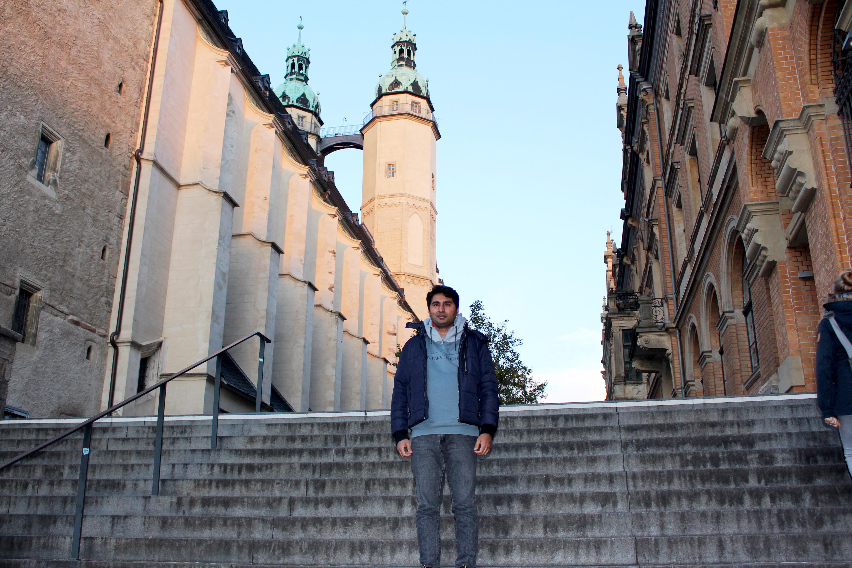 Ein Mann steht auf einer Treppe, hinter ihm eine Kirche.
