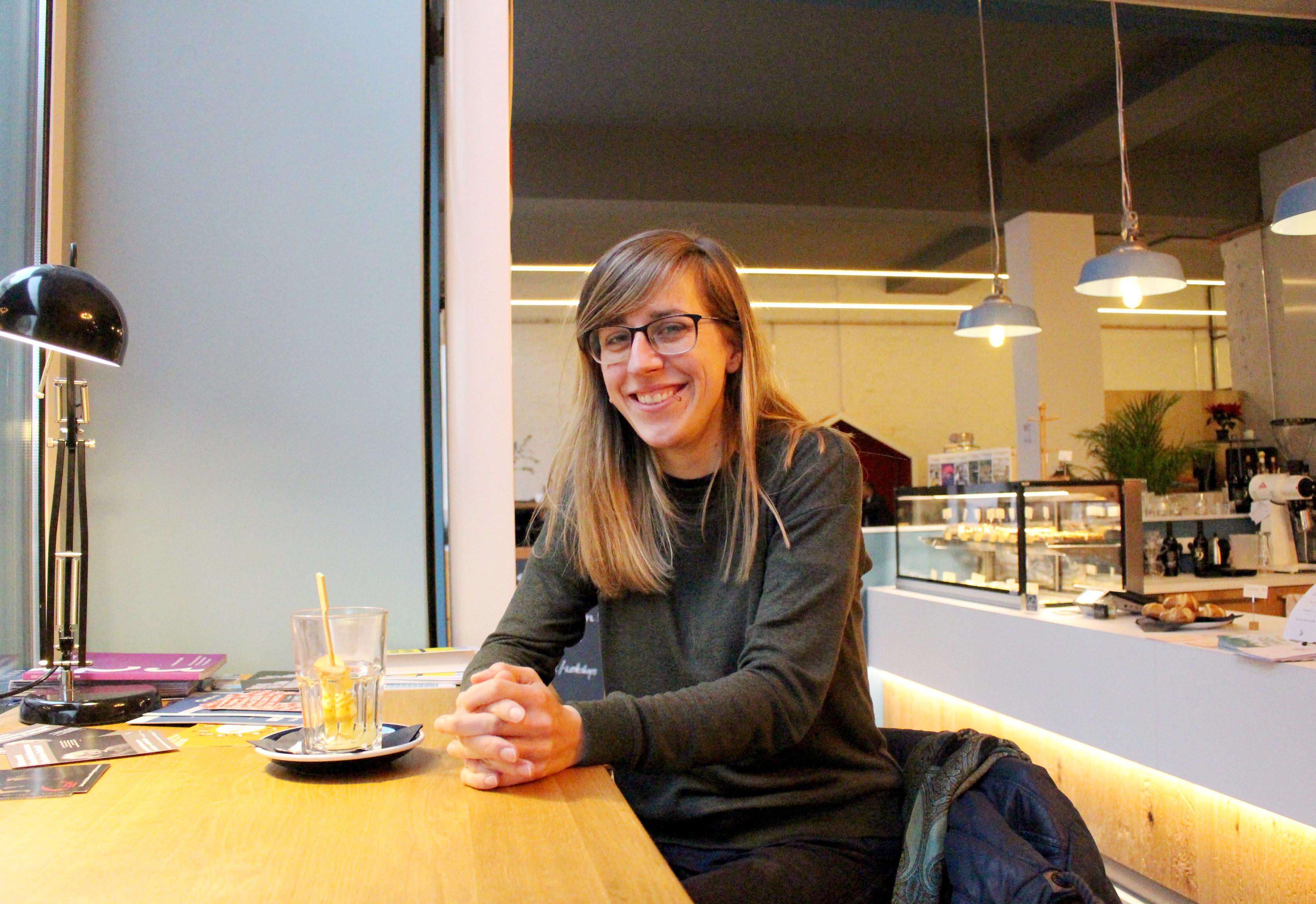Eine Frau sitzt an einem Tresen in einem Café.