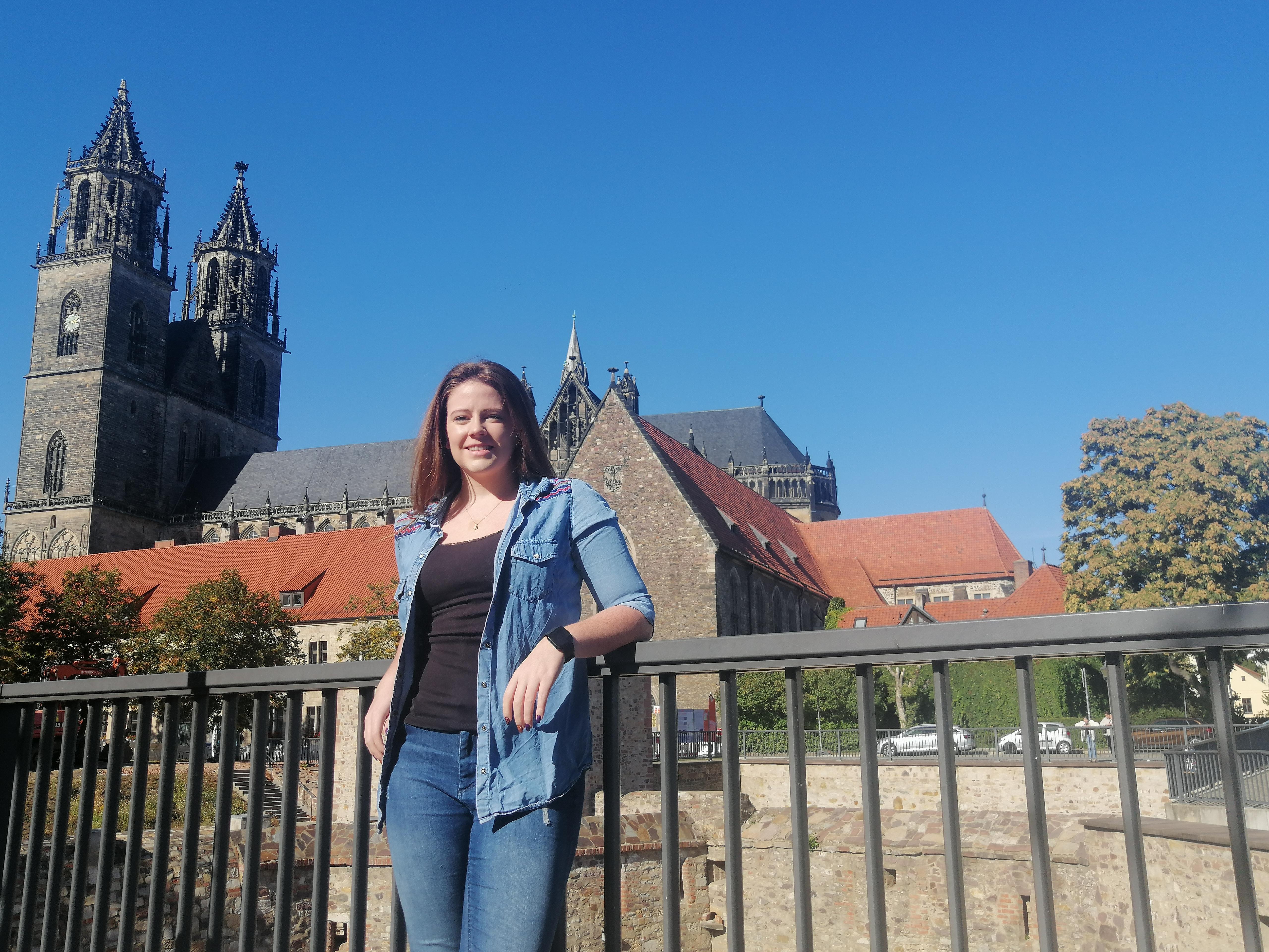 Rachel Neal steht an einem Zaun, im Hintergrund ist eine Kirche. (Foto: Rachel Neal)