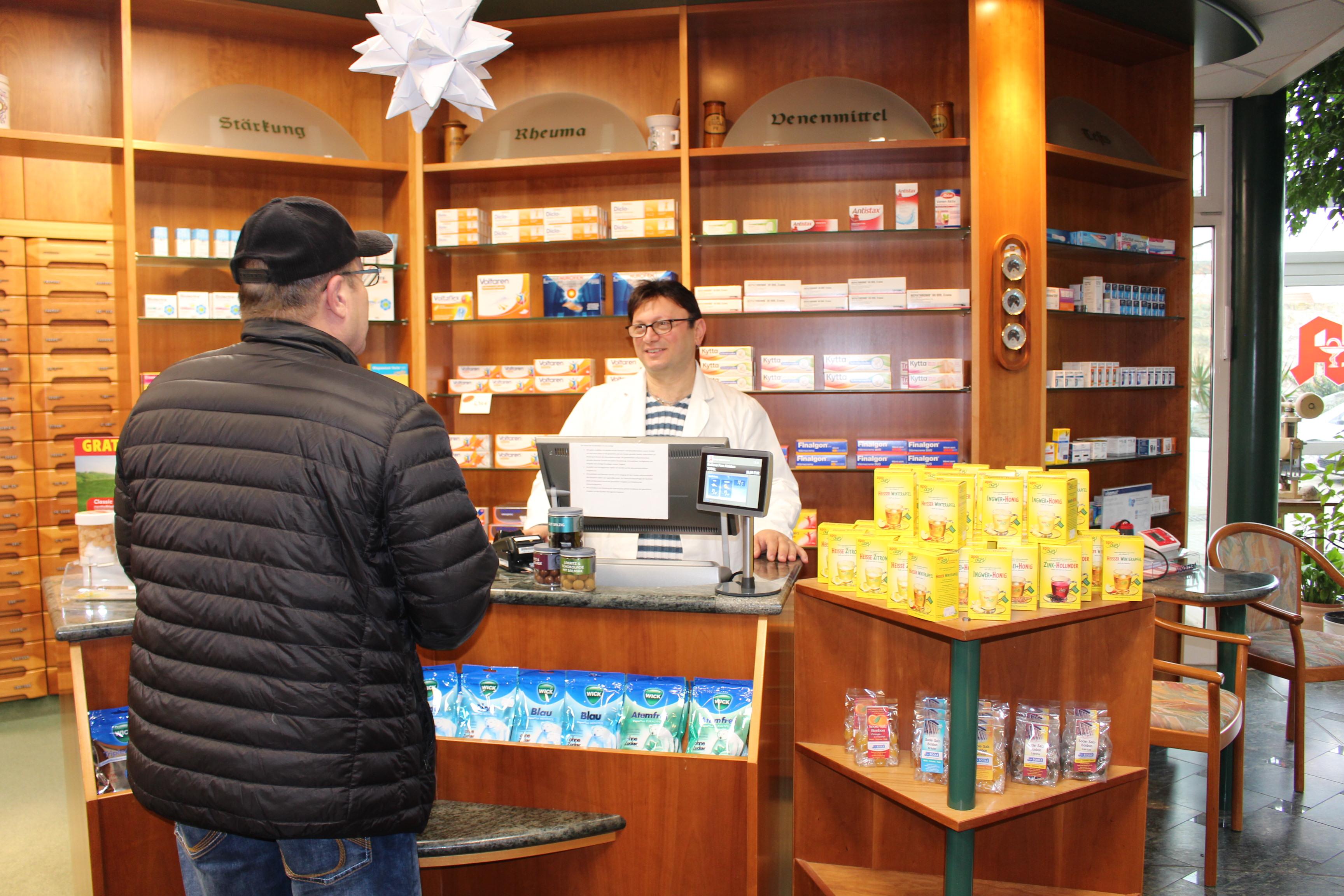 Wartan Wartanian steht hinter dem Tresen in einer Apotheke und bedient einen Kunden.