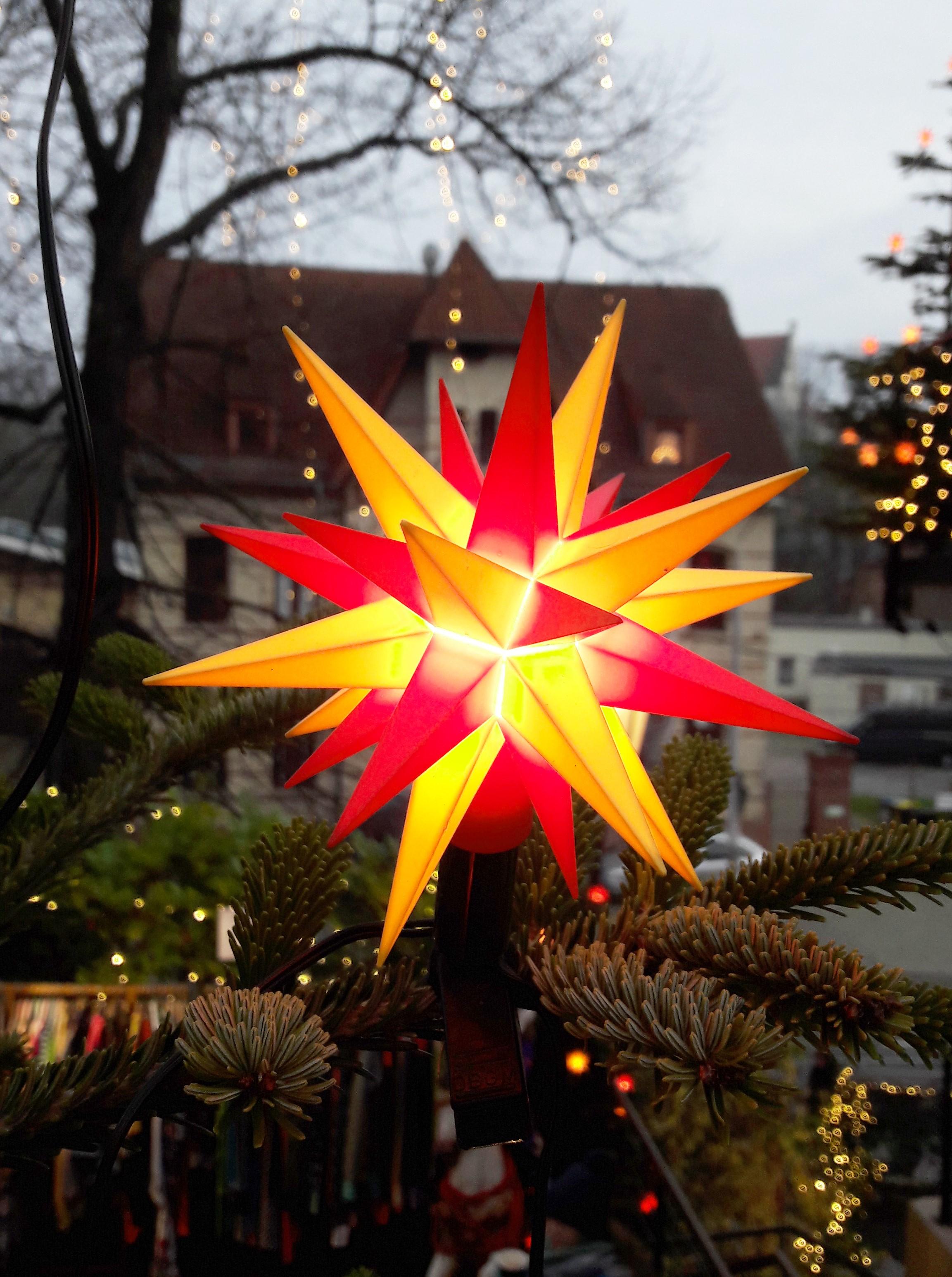 Ein kleiner leuchtender Stern hängt im Weihnachtsbaum, Hintergrund ein Haus und Straße